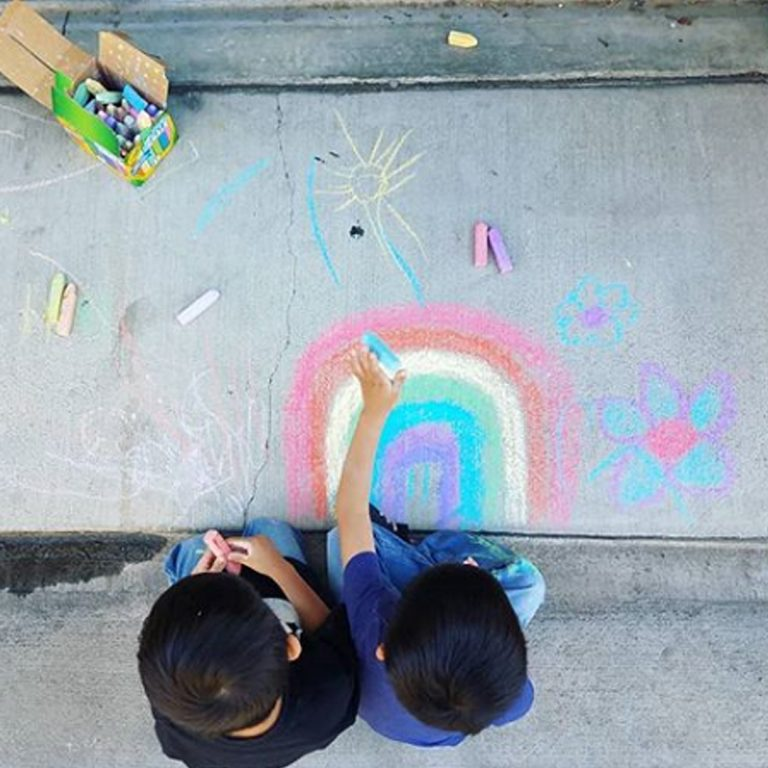 twin boys on sidewalk drawing rainbow